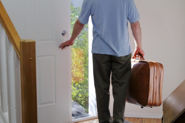 Picture of man exiting home with suitcase
