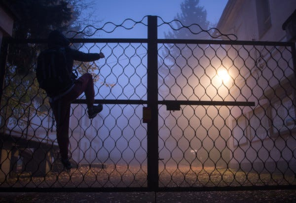 Picture of person climbing over gate at night