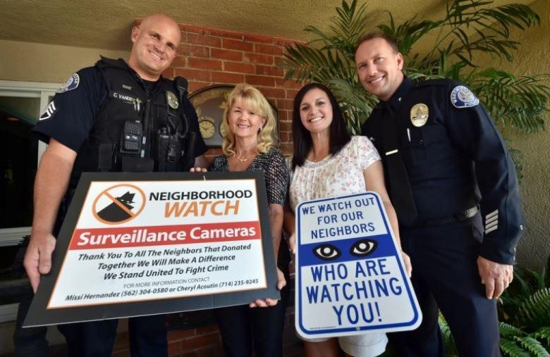 Photo of neighborhood members with police officers holding neighborhood watch signs